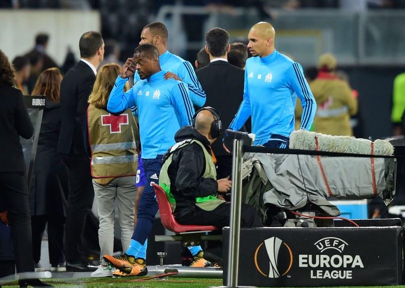 Patrice Evra (L) opuszcza murawę po starciu z kibicami /AFP