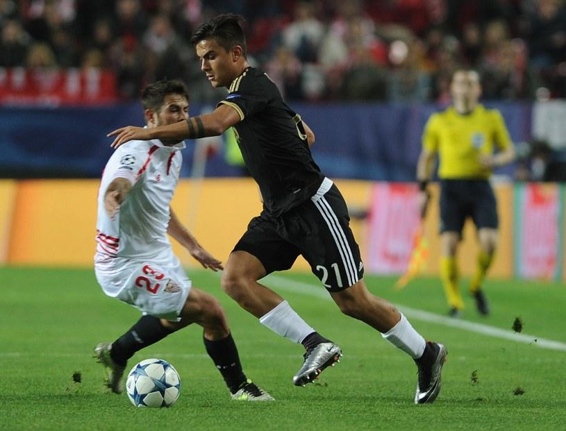 Paulo Dybala z Juventusu (czarny strój) mija Coke z Sevilli /AFP