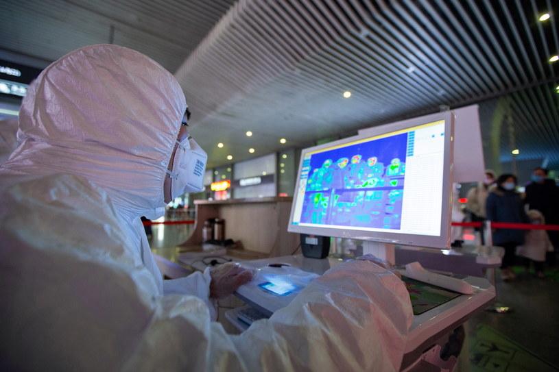 Personel medyczny sprawdza temperaturę ciała podróżnych w Chinach w celu wykrycia zakażonych koronawirusem /SU YANG CHINA OUT /PAP/EPA