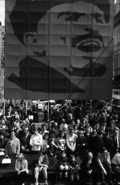 Warszawa, 01.05.1975, ludzie oglądają pierwszomajowy pochód, siedząc pod wielkim portretem Lenina na ul. Marszałkowskiej
