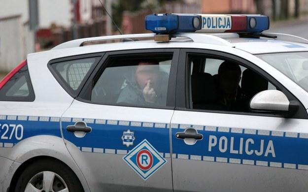 Pijany kierowca opla pokazuje gest fuck you siedzac w radiowozie drogowki /Fot. Piotr Jedzura /Reporter