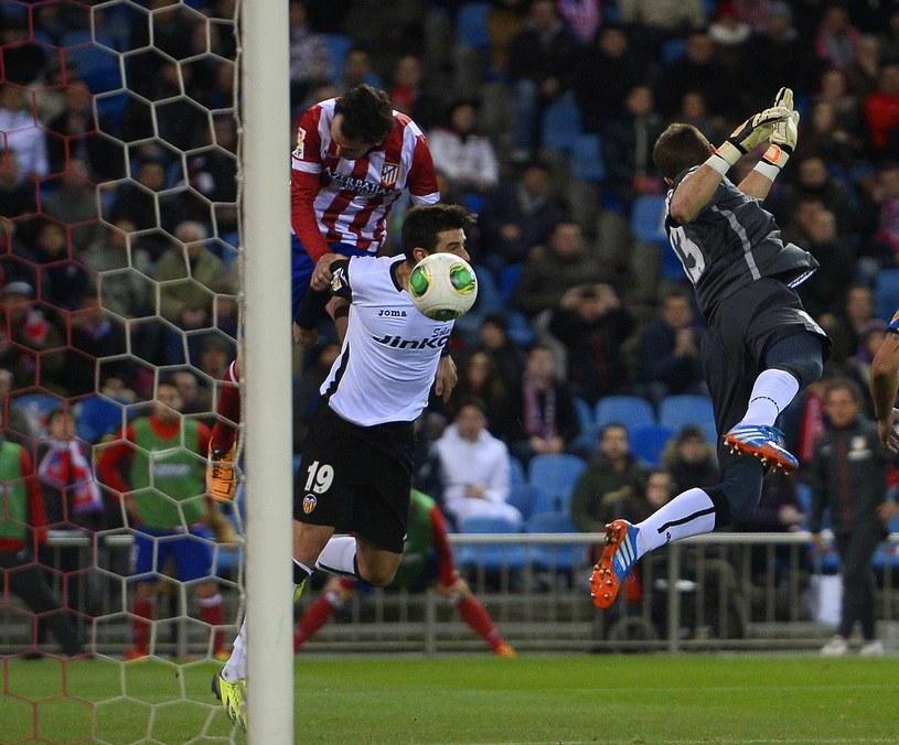 Piłkarz Atletico Madryt Diego Godin (u góry z lewej) strzela gola mimo asysty obrońcy Valencii Antonio Barragana /AFP