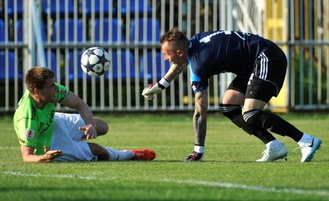Piłkarz Dolcanu Ząbki Grzegorz Piesio (L) atakuje bramkarza PGE Skry Bełchatów Arkadiusza Malarza /Bartłomiej Zborowski  /PAP /PAP