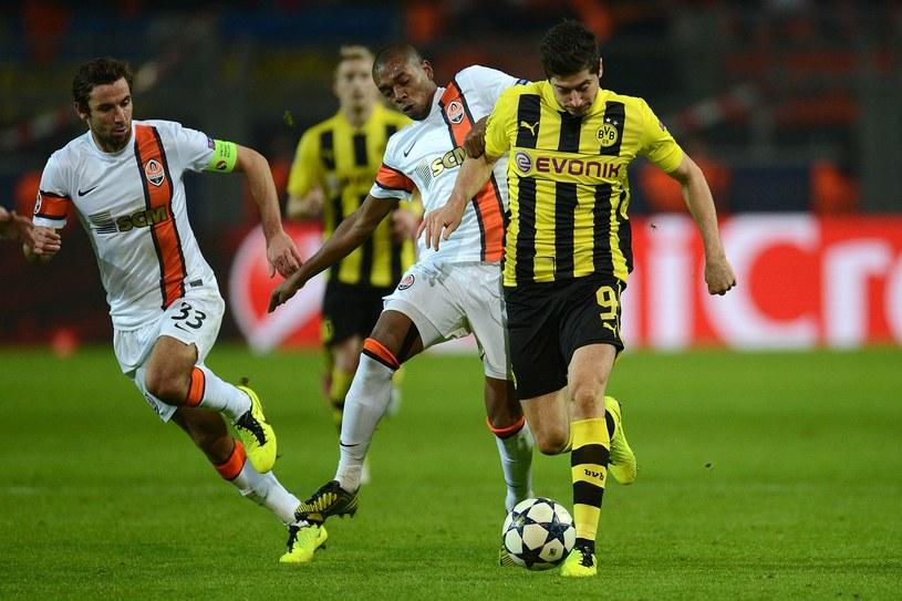 Piłkarz Szachtara Donieck Fernandinho atakuje Roberta Lewandowskiego z Borussii Dortmund /AFP