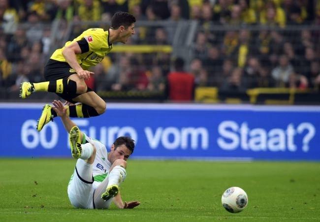 Piłkarz VfL Wolfsburg Christian Traesch próbuje zatrzymać Roberta Lewandowskiego z Borussii Dortmund (u góry) /PAP/EPA