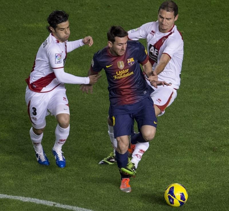 Piłkarze Rayo próbują powstrzymać gwiazdę Barcelony Lionela Messiego /AFP