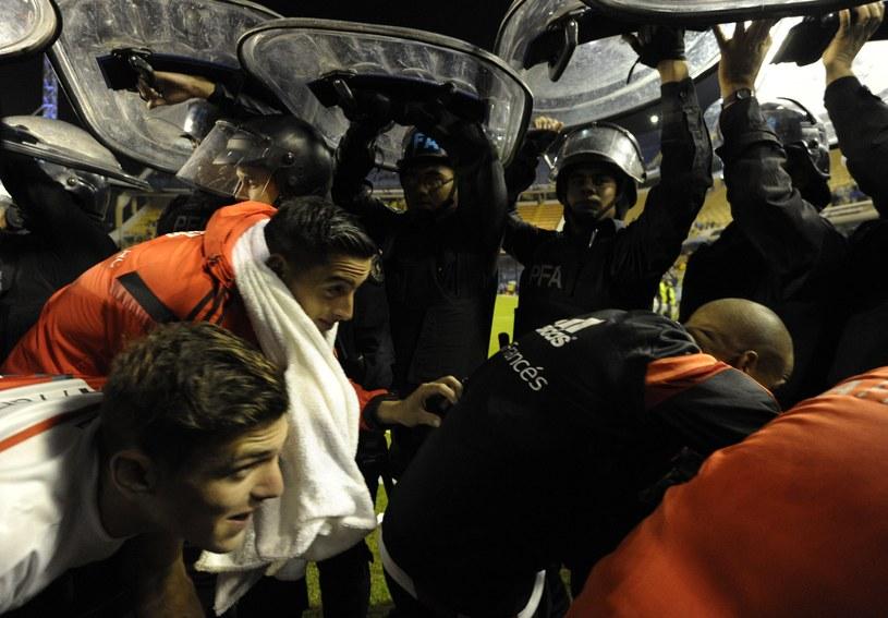 Piłkarze River Plate opuszczają boisko pod ochroną policji /AFP