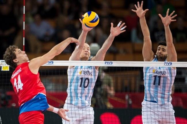 Piłkę zbija Serb Aleksandar Atanasijević (L), blokują Argentyńczycy Jose Luis Gonzalez (C) i Sebastian Sole /Maciej Kulczyński /PAP