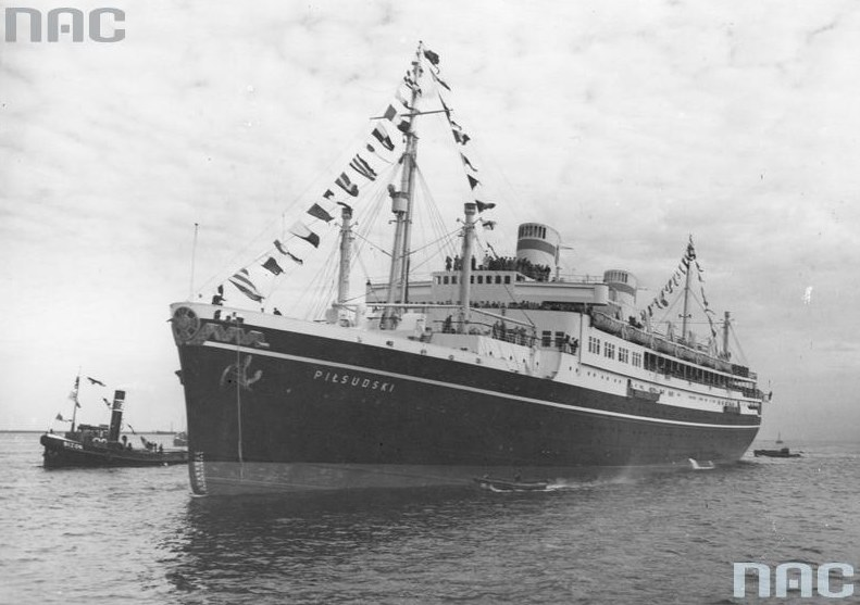 """""""Piłsudski"""" w gali flagowej pilotowany przez holownik """"Bizon"""" wpływa do portu /Z archiwum Narodowego Archiwum Cyfrowego"""