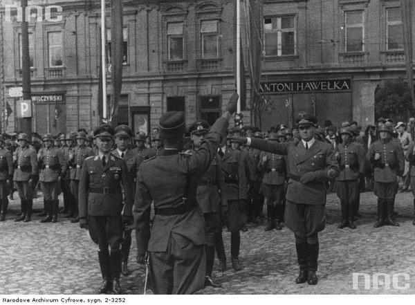 Gubernator Hans Frank przyjmuje raport na placu Adolfa Hitlera (obecnie Rynek Główny) w Krakowie. Na drugim planie widoczna kompania honorowa