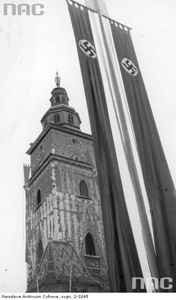 Maszt z flagą III Rzeszy. W tle widoczna wieża ratuszowa w Krakowie przystrojona flagami III Rzeszy