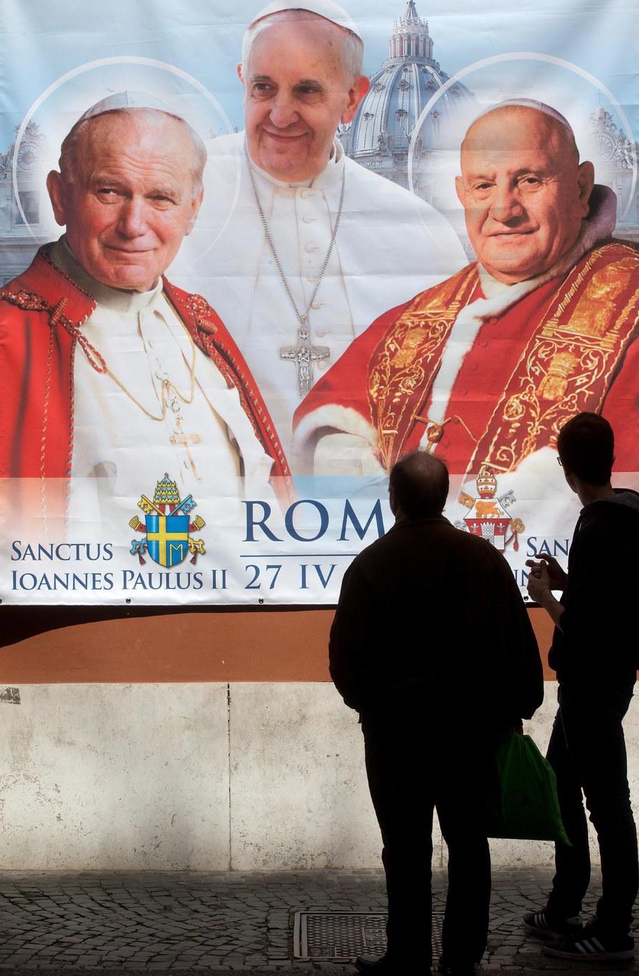 Plakat z wizerunkami Jana Pawła II (po lewej), Jana XXIII (po prawej) i Franciszka w Rzymie /CLAUDIO PERI /PAP/EPA