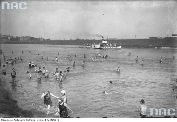Plaża nad Wisłą w Krakowie. Plażowicze podczas kąpieli. W tle widoczny statek parowy, 1927