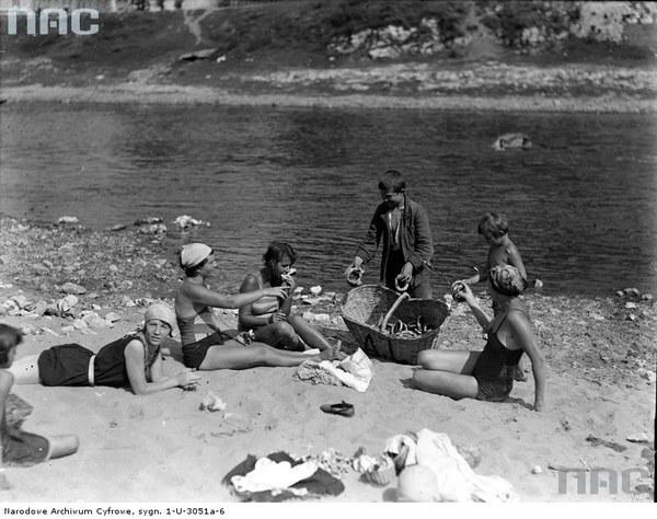 Kraków. Plaża nad Wisłą. Plażowicze podczas wypoczynku. Widoczny chłopiec sprzedający bajgle, 1929