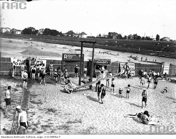 Plaża Towarzystwa Uniwersytetu Robotniczego w Krakowie. Plażowicze podczas wypoczynku. Widoczne huśtawki, 1933