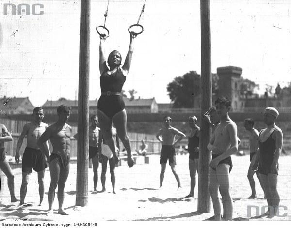 Plaża Towarzystwa Uniwersytetu Robotniczego w Krakowie. Kobieta na huśtawce oraz inni plażowicze podczas zabawy i wypoczynku, 1931