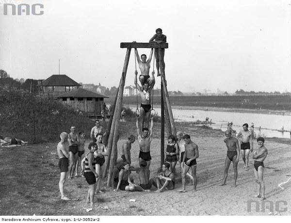 Plaża nad Wisłą w Krakowie. Plażowicze podczas wypoczynku i zabawy na huśtawce, 1929