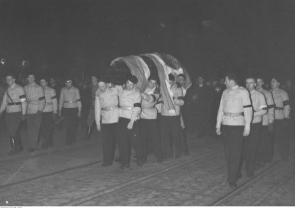 Członkowie Ruchu Narodowo-Radykalnego Falanga (ubrani w stroje obozowe) niosą na ramionach trumnę ze zwłokami Romana Dmowskiego