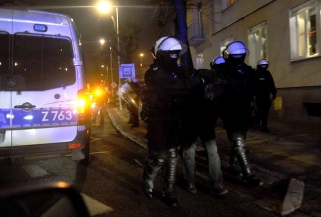 Policja prowadzi do radiowozu jednego z zatrzymanych kibiców /Bartłomiej Zborowski /PAP