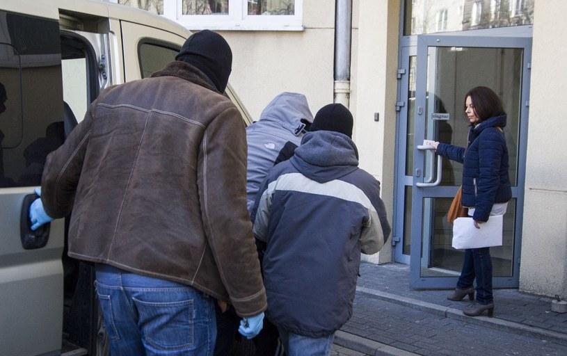 Policjanci prowadzą osobę podejrzaną o pedofilię, zdjęcie ilustracyjne /Krystian Dobuszyński /Reporter