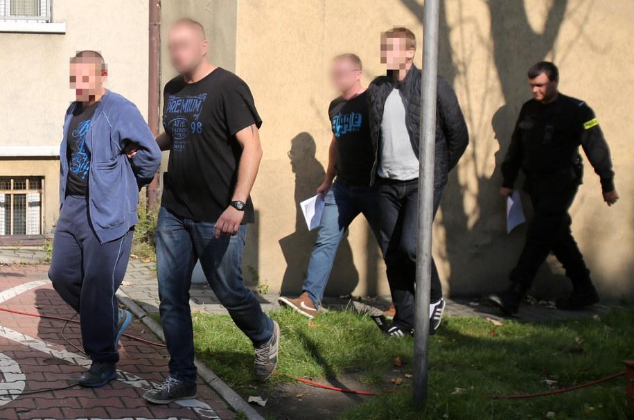 Policjanci wyprowadzają z Komendy Miejskiej Policji w Chorzowie dwóch mężczyzn podejrzanych o podłożenie ładunku zapalającego na stadionie chorzowskiego Ruchu /Andrzej Grygiel   (PAP) /PAP