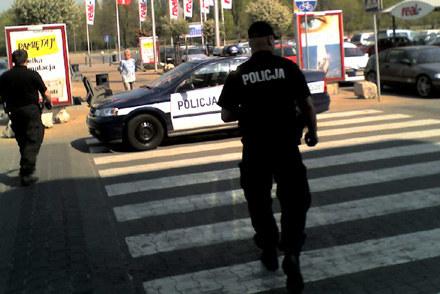 Policjant chowa za siebie białą siatkę. Za chwilę włoży ją do  bagażnika / kliknij /INTERIA.PL