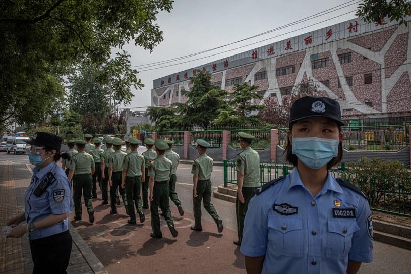 Policjantka przed budynkiem zamkniętego rynku Xinfadi w Pekinie /ROMAN PILIPEY /PAP/EPA