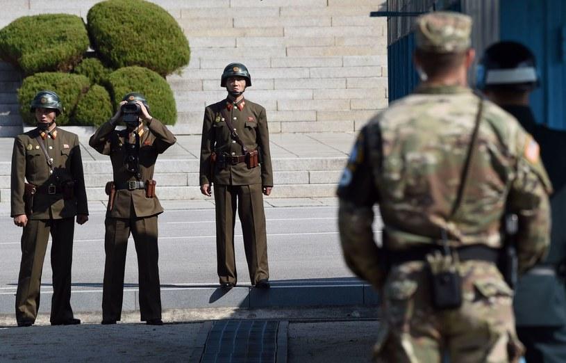 Północnokoreańscy żołnierze zerkają na amerykańskiego żołnierza, który znajduje się po stronie Korei Południowej. /AFP