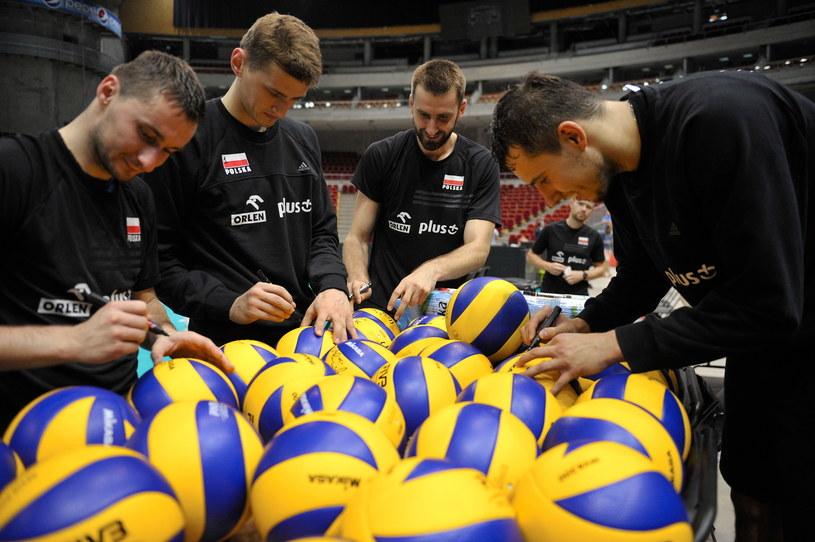 Polscy siatkarze podpisują piłki podczas treningu w Ergo Arenie /Fot. Adam Warżawa /PAP