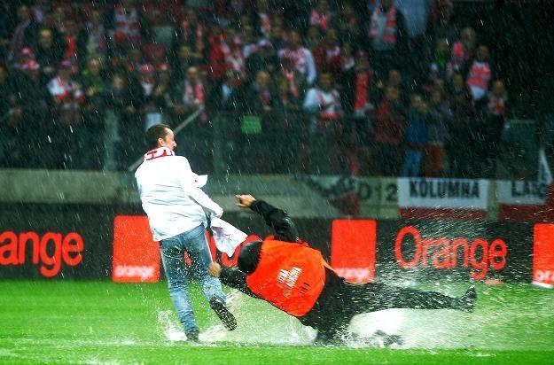 Polski kibic i ochrona w pościgu na zalnym wodą boisku przed meczem /fot. B. Zborowski /PAP