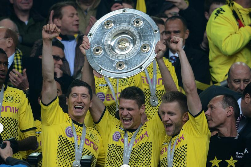 """Polskie """"trio z Dortmundu"""" świętuje tytuł mistrzowski w 2012 roku. Od lewej: Robert Lewandowski, Łukasz Piszczek i Jakub Błaszczykowski /PATRIK STOLLARZ /AFP"""