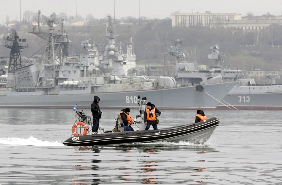 Port w Sewastopolu: Rosyjscy żołnierze na łodzi patrolowej, w tle okręty bojowe Floty Czarnomorskiej /MAXIM SHIPENKO /PAP/EPA