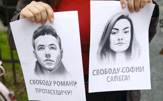 Portrety Pratasiewicza i Sapiegi trzymane przez jedną z demonstrujących w Rydze /TOMS KALNINS  /PAP/EPA