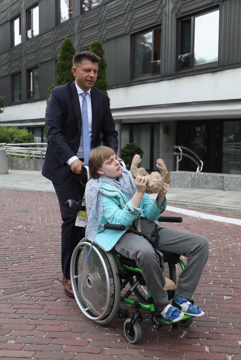 Poseł Ryszard Petru i jedna z niepełnosprawnych dziewczynek, uczestniczek protestu w Sejmie, z maskotką przekazaną przez Wandę Traczyk-Stawską /Paweł Supernak /PAP