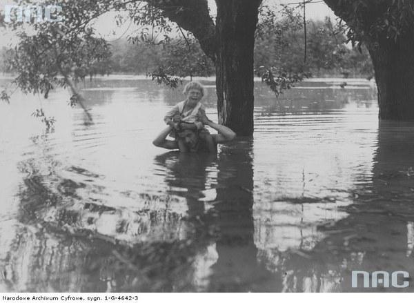 Powódź pod Warszawą. Mężczyzna przenosi na barkach dziecko z zalanej chałupy, 1934