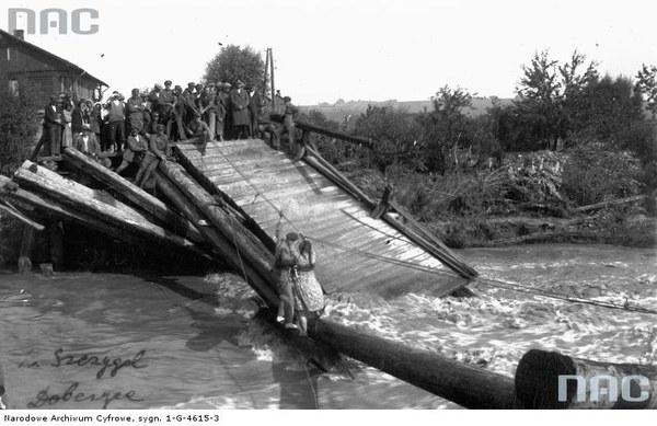 Powódź w Dobczycach. Zerwany most na Rabie. Żołnierz trzymając się jedną ręką liny pomaga kobiecie przejść na drugi brzeg rzeki
