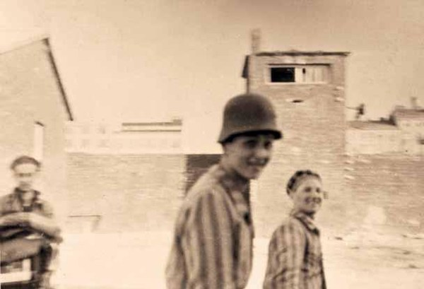 """Trzej uwolnieni Żydzi na tle jednej z wież strażniczych niemieckiego obozu koncentracyjnego, tzw. Gęsiówki. 5.08 o godz. 10.37 dwa plutony Batalionu """"Zośka"""" zaatakowały obóz koncentracyjny."""
