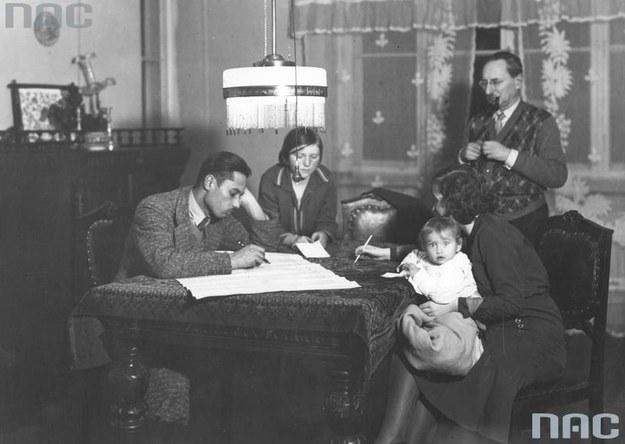 Powszechny Spis Ludności (zdjęcie z 1931 roku): Rodzina z pomocą komisarza spisowego wypełnia arkusz spisowy. /Z archiwum Narodowego Archiwum Cyfrowego