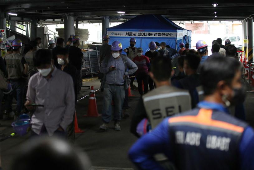 Pracownicy budowlani czekają na testy COVID-19 na terenie przebudowy hotelu w Seulu /YONHAP   /PAP/EPA