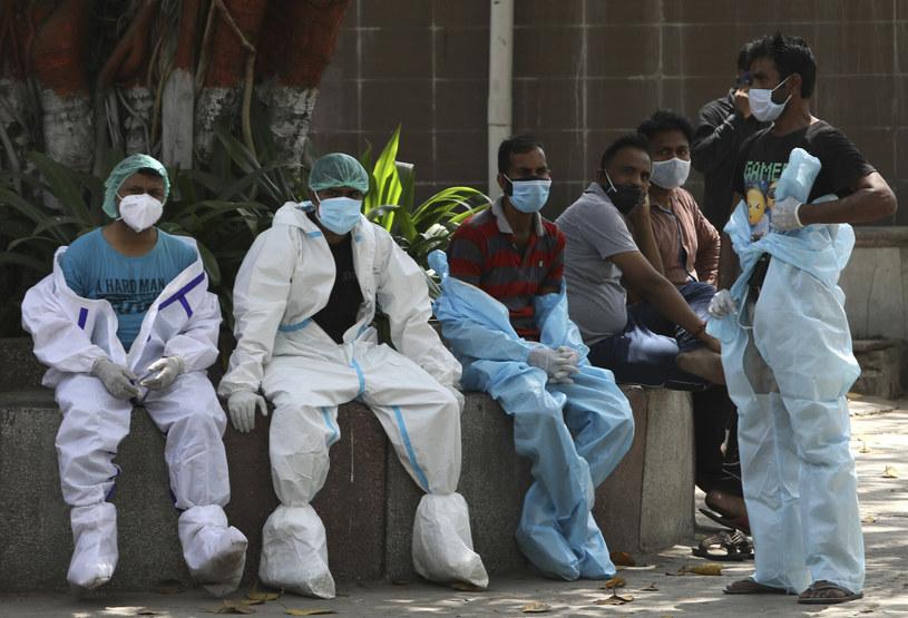 Pracownicy indyjskiej służby zdrowia w New Delhi odpoczywają w przerwie między kolejnymi kremacjami ciał pacjentów zmarłych na COVID-19 /AP/Associated Press/East News /East News