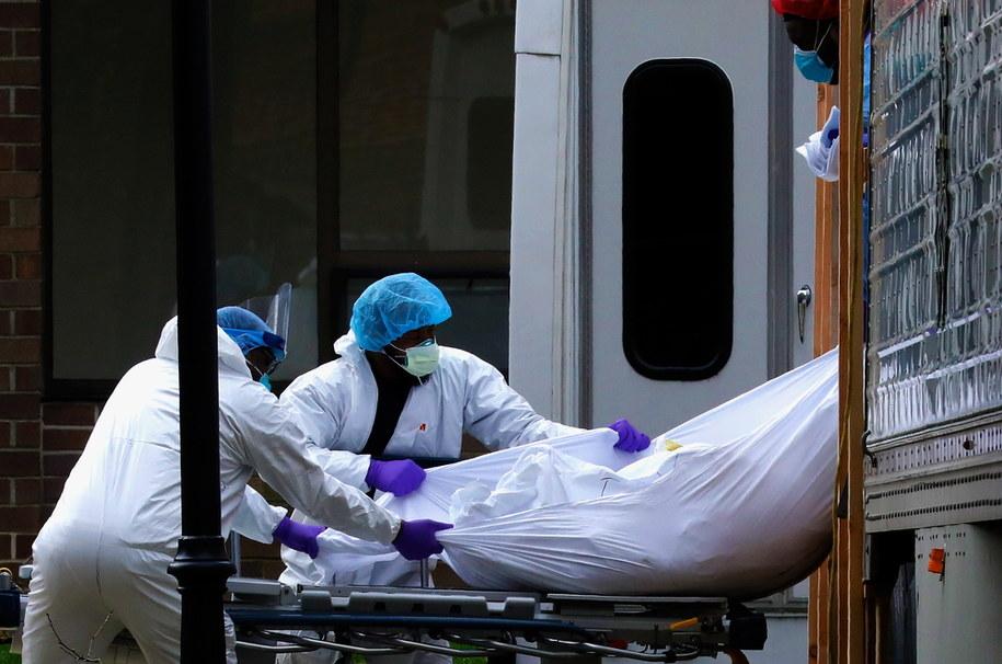 Pracownicy medyczni wyjmują ciało ofiary koronawirusa z ciężarówki-chłodni, Nowy Jork /Peter Foley /PAP/EPA