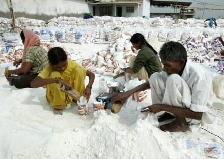 Pracownicy w Indiach pakują sól do woreczków /AFP