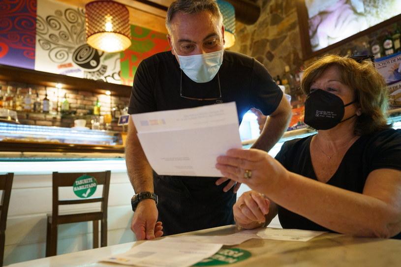 Pracownik baru na Wyspach Kanaryjskich sprawdza paszport covidowy /RAMON DE LA ROCHA /PAP/EPA
