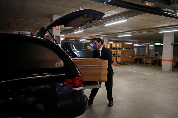 Pracownik domu pogrzebowego ładujący trumnę do karawanu /QUIQUE GARCIA /PAP/EPA