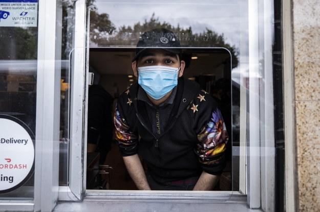 Pracownik restauracji w maseczce ochronnej /ETIENNE LAURENT /PAP/EPA