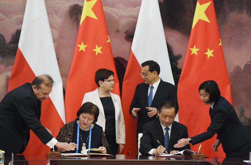 Premier Beata Szydło (L, centrum) oraz premier ChRL Li Keqiang (P, centrum) podczas podpisania umowy o współpracy w dziedzinie turystyki pomiędzy wiceminister Joanną Wronecką (2L) i Li Jinzao (2P) /Radek Pietruszka /PAP