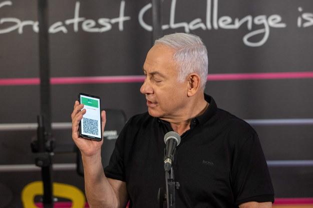 Premier Izraela Benjamin Netanjahu podczas konferencji prasowej przed otwarciem m.in. siłowni. Na telefonie pokazuje aplikacje poświadczającą zaszczepieni /Tal Shahar / POOL /PAP/EPA