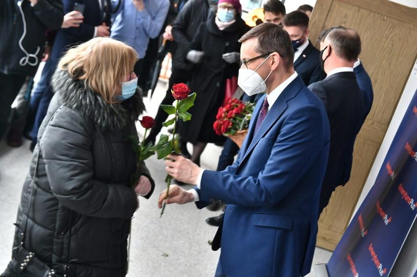 Premier Mateusz Morawiecki rozdaje kwiaty z okazji Dnia Kobiet po uroczystości podpisania przez Prezydenta RP ustawy z dnia 21 stycznia 2021 roku o kolejnym w 2021 roku dodatkowym rocznym świadczeniu pieniężnym dla emerytów i rencistów w Otwocku