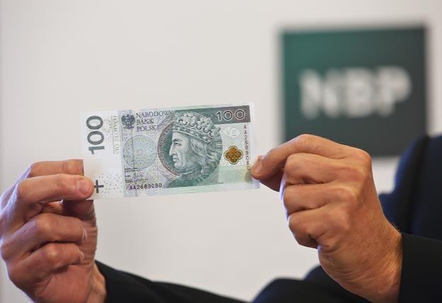 Prezes Narodowego Banku Polskiego Marek Belka prezentuje banknot stuzłotowy /PAP
