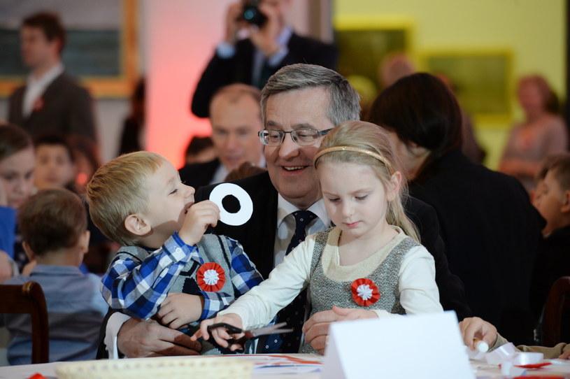 Prezydent Bronisław Komorowski z dziećmi przybyłymi na spotkanie robi kokardy narodowe /Jacek Turczyk /PAP